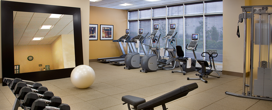 A spacious exercise room with treadmills, bikes, and weights at the Hilton Garden Inn in Toronto