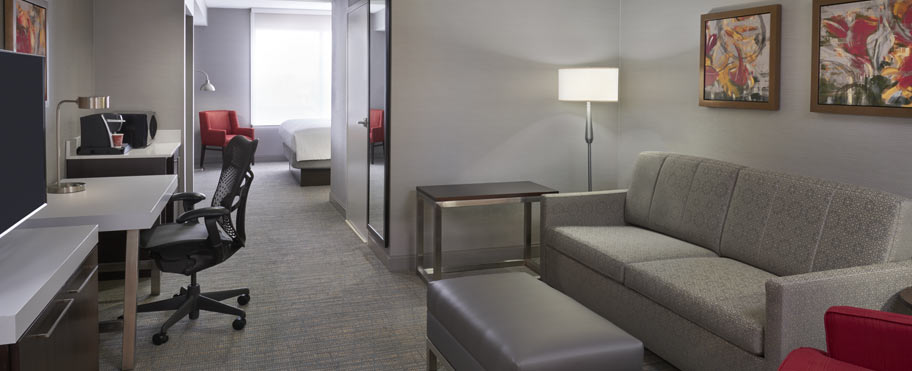A spacious room with a large tv, desk, large sofa, microwave, and fridge at the Hilton Garden Inn in Mississauga